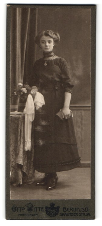 Fotografie Otto Witte, Berlin, Frau im Kleid mit Tuch und Geldbörse in der Hand