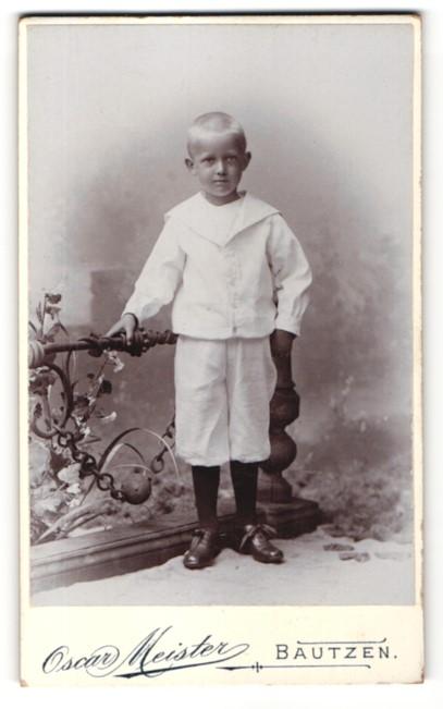 Fotografie Oscar Meister, Bautzen, Kleiner Junge in weissen Klamotten steht am Geländer