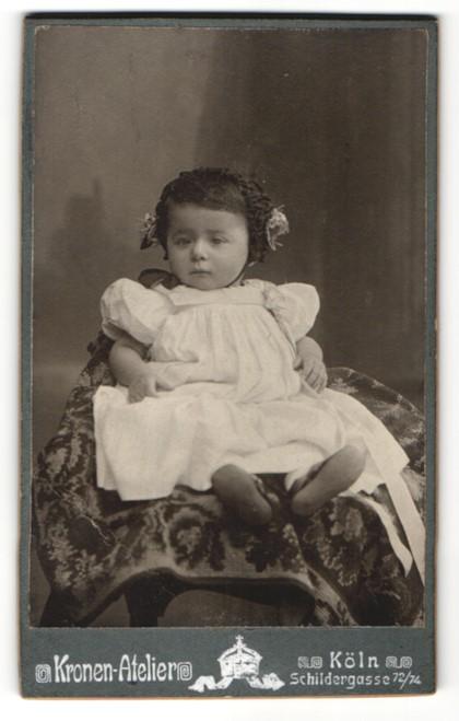 Fotografie Kronen Atelier, Köln, Baby im Kleidchen auf Stuhl sitzend