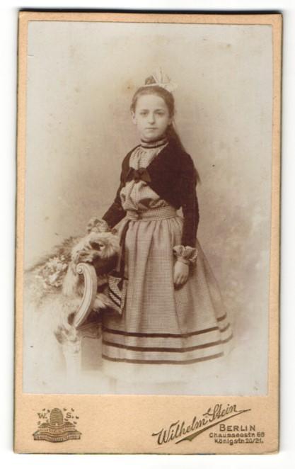 Fotografie Wilhelm Stein, Berlin, Mädchen im Kleid stehend vor Stuhl