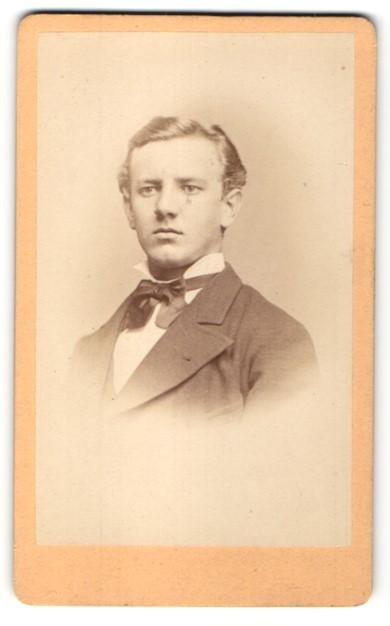 Fotografie Julius Zschille, Berlin, Portrait junger Mann im Anzug mit Fliege