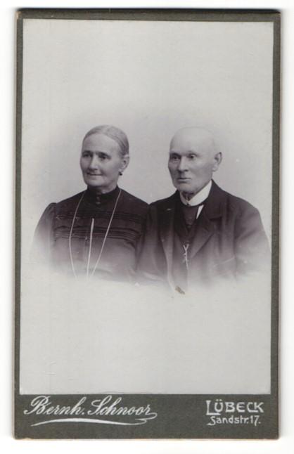 Fotografie Bernh. Schnoor, Lübeck, Portrait betagtes Paar in zeitgenöss. Kleidung