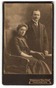 Fotografie Hermann Schlüter, Magdeburg, Ehepaar wohl gekleidet im Foto-Atelier