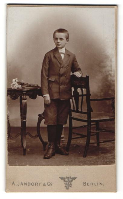 Fotografie A. Jandorf & Co, Berlin, frecher Bube mit kurzem Haar und Schürstiefeln im Anzug