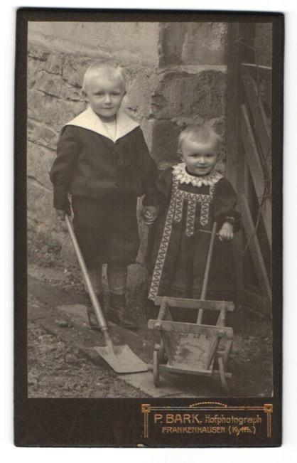 Fotografie P. Bark, Frankenhausen, Portrait Bub mit Schaufel und kleine Schwester mit Bollerwagen