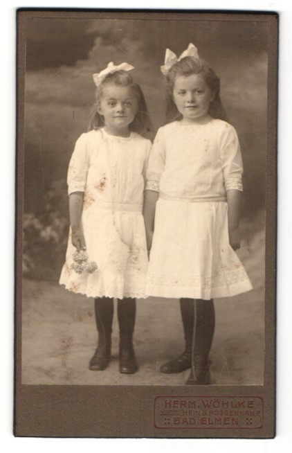 Fotografie Herm. Wöhlke, Bad Elmen, Portrait zwei kleine Mädchen in Kleidern mit Haarschleife