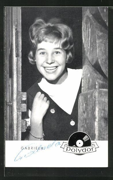 AK Musikerin Gabriela lächelnd an einer Tür stehend mit Autogramm