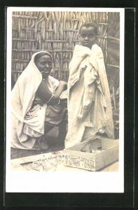 AK Afrikanische Mutter mit ihrem Kind in einer Hütte
