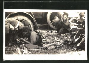 AK Swaziland, Mann im Leopardenfell am Reifen eines Autos
