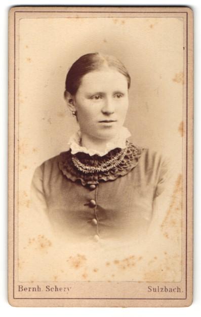 Fotografie Atelier Bernh. Schery, Sulzbach, Frau mit zurückgekämmten Haaren und dunkler Bluse mit weissem Kragen