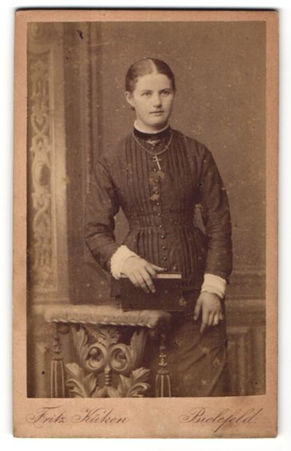 Fotografie Atelier Fritz Küken, Bielefeld, stehende junge Frau mit elegantem Kleid und Kreuzkette