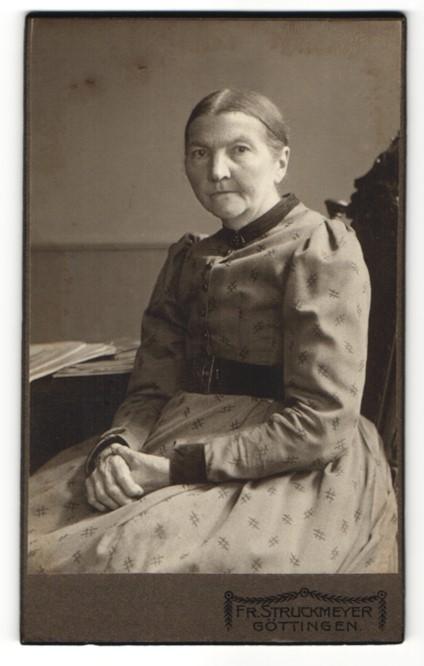 Fotografie Atelier Fr. Struckmeyer, Göttingen, ältere sitzende Frau mit hellem gemusterten Kleid