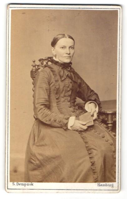 Fotografie Atelier S. Dempzok, Hamburg, sitzende Frau mit elegantem dunklen Kleid
