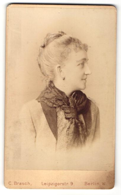 Fotografie Atelier C. Brasch, Berlin, Frau mit hochgekämmter Frisur, heller Jacke und dunklem Halstuch von der Seite