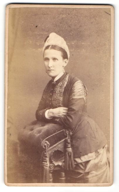 Fotografie Atelier W. Runicles & Sons, Windsor, stehende Frau mit dunkler Jacke und hellem Hut auf Hocker gelehnt