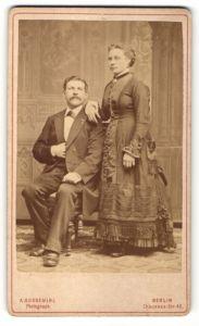 Fotografie A. Sussemihl, Berlin, Mann im Anzug sitzend neben Frau im Kleid stehend