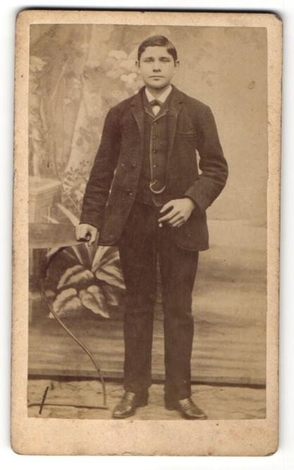Fotografie Fotograf unbekannt, Ort unbekannt, Junger Mann im Anzug an Tisch stehend
