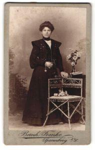 Fotografie Bernh. Franke, Spremberg, Junge Frau im Kleid an Stuhl stehend