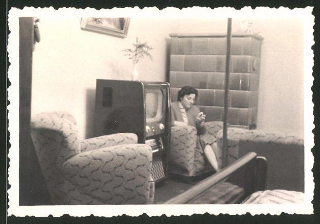 Fotografie TV-Gerät, Hausfrau neben Fersehapparat sitzend