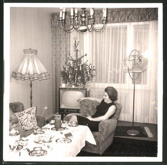 Fotografie TV-Gerät, Hausfrau zu Weihnachten neben Fernsehgerät sitzend