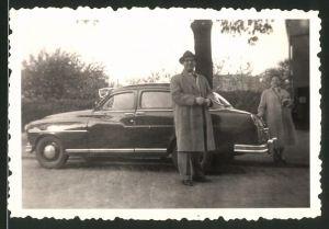 Fotografie Auto, stolzer Fahrer neben Limousine mit Sonnenblende