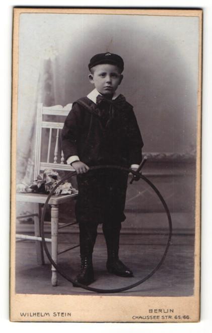 Fotografie Wilhelm Stein, Berlin, Portrait Knabe mit Holzreifen