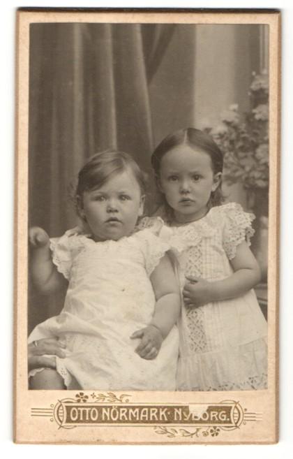 Fotografie Otto Nörmark, Nyborg, zwei bezaubernd süsse Mädchen in weissen Kleidchen mit Stickerei