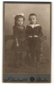 Fotografie A. Jandorf & Co., Berlin, Portrait Knabe und Mädchen mit Holzreifen