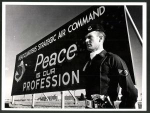 Fotografie USIS, Ansicht Offutt Air Force Base / Nebraska, Sgt. in Uniform neben Schild: Peace is our profession