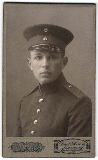 Fotografie Paul Kruse, Hamburg, Portrait hübscher junger Soldat mit Schirmmütze in Uniform, Nummer 9 auf der Schulter