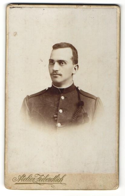 Fotografie Atelier Zeiberdlich, Terezin, Portrait charmanter dunkelhaariger Soldat in interessanter Uniform