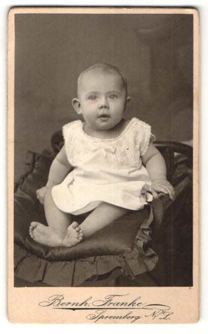Fotografie Bernh. Franke, Spremberg, zuckersüsses Baby mit grossen Augen im weissen Kleidchen