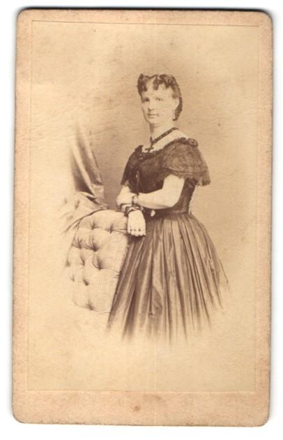 Fotografie Albert Grundner, Berlin, charmant blickende junge Frau mit lockigem Haar im prachtvollen Kleid