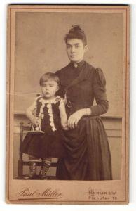 Fotografie Paul Müller, Berlin, hübsche dunkelhaarige Frau im schwarzen Kleid mit süssem Mädchen im bestickten Kleid
