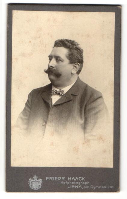 Fotografie Friedrich Haack, Jena, Portrait stattlicher dunkelhaariger Herr mit Oberlippenbart und Fliege im Jackett
