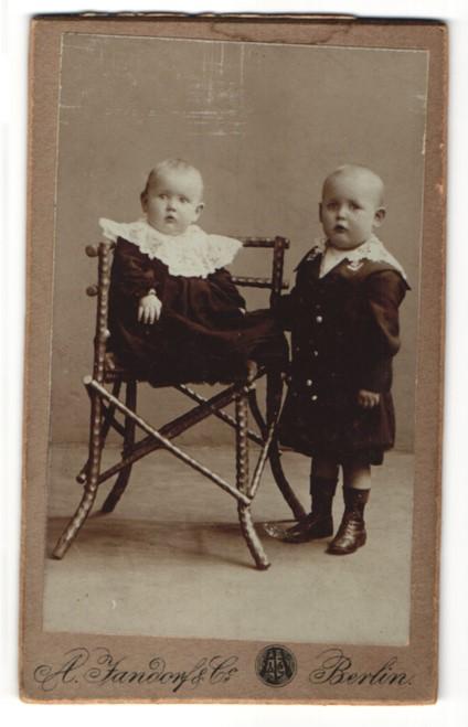 Fotografie A. Jandorf & Co., Berlin, zwei bezaubernd süsse Kleinkinder in dunklen Kleidern mit weissen Spitzenkragen