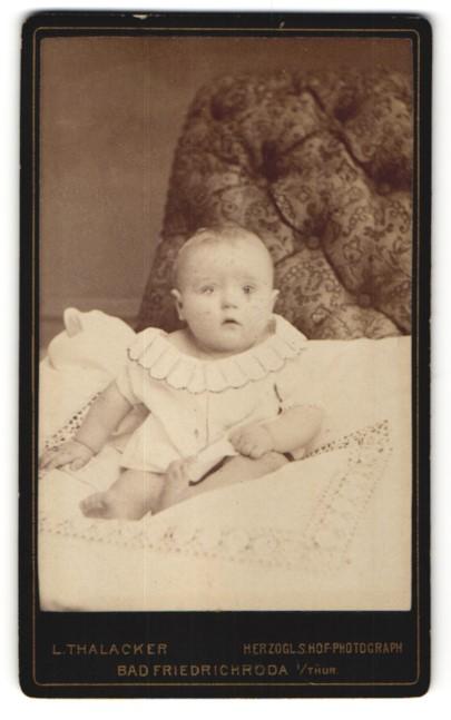 Fotografie L. Thalacker, Bad Friedrichroda / Thür., zuckersüsses Baby mit grossen Augen im weissen Kleidchen