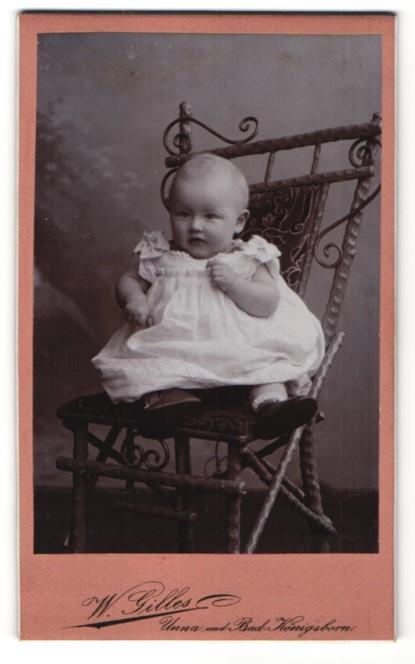 Fotografie W. Gilles, Unna, zuckersüsses Baby im weissen Kleidchen mit Schühchen