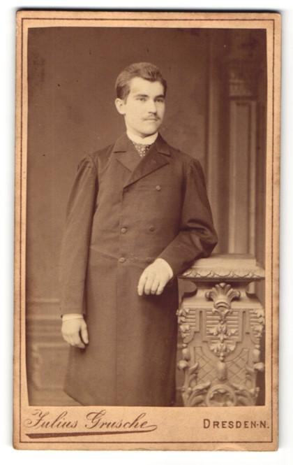 Fotografie Julius Grusche, Dresden-N., charmanter junger Mann mit Schnauzer im Mantel