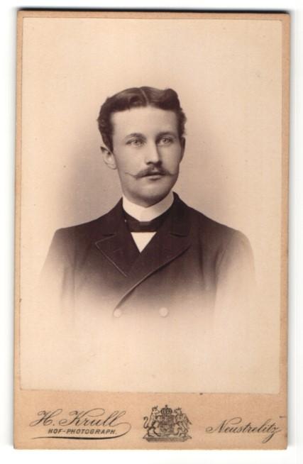 Fotografie H. Krull, Neustrelitz, Portrait charmanter junger Mann mit Mittelscheitel und Schnauzer im Jackett