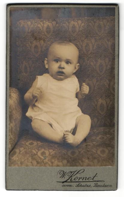 Fotografie W. Kornet, Bautzen, zuckersüsses Baby im weissen Hemdchen im Sessel sitzend