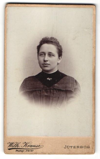 Fotografie Wilh. Krause, Jüterbog, Portrait charmant blickende junge Frau mit Brosche am Kragen