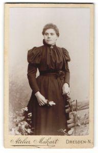 Fotografie Atelier Makart, Dresden-N., Portrait brünette junge Schönheit im schwarzen Rüschenkleid mit Blume in der Hand