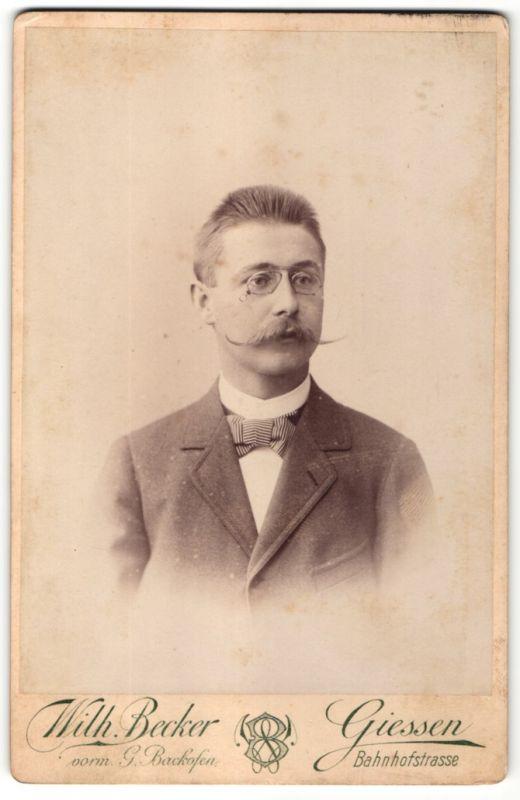 Fotografie Wilh. Becker, Giessen, Portrait junger Herr mit imposantem Schnauzbart und Zwicker