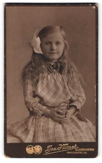 Fotografie Jos. Minet, Elmshorn, Mädchen mit Haarband in kariertem Kleid