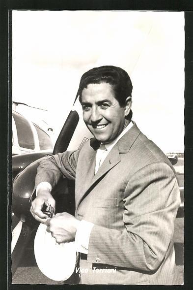 AK Schauspieler Vico Torriani lächelnd an einem Flugzeug stehend