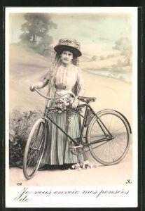 AK Frau Hut steht neben ihrem Fahrrad