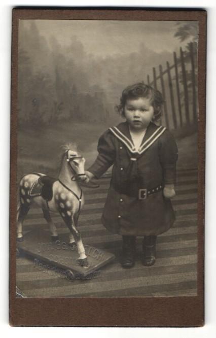 Fotografie J. G. Gmelch, Schongau, Mädchen in Marine-Uniform mit Spielzeug-Pferd