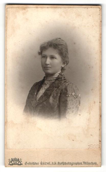 Fotografie Gebr. Lützel, München, Portrait junge Frau in festlicher Kleidung mit zurückgekämmten Haaren