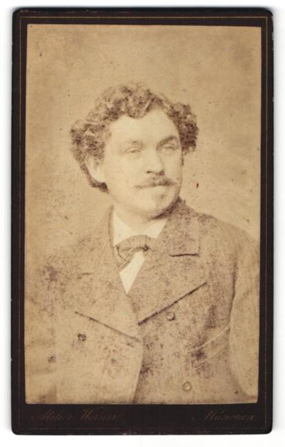 Fotografie Atelier Werner, München, Portrait Mann mit Locken und Schnauzbart im Anzug